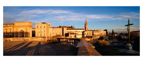 Montpellier - L'Arc de triomphe et le clocher de l'église Saint Anne, depuis les jardins du Pérou. Carte Postale panoramique 10x23. Photographe Marianne Raous