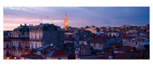 Montpellier - Crépuscule sur les toits de la vieille ville. Carte Postale panoramique 10x23. Photographe Marianne Raous
