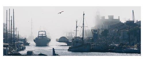Le Grau du Roi, Le canal et le vieux phare sous la brume. Carte postale panoramique 10x23 cm. Photographe: Marianne Raous
