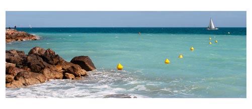 Palavas - La Plage, la mer turquoise, bouées jaunes, voilier. Carte postale panoramique 10x23 cm - Photographe: Marianne Raous