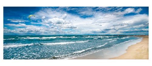 Port Camargue - La plage par grand vent - Kite surf -  mistral. Au loin, la sortie du Port depuis la plage sud. Carte postale panoramique 10x23 cm - Photographe: Marianne Raous